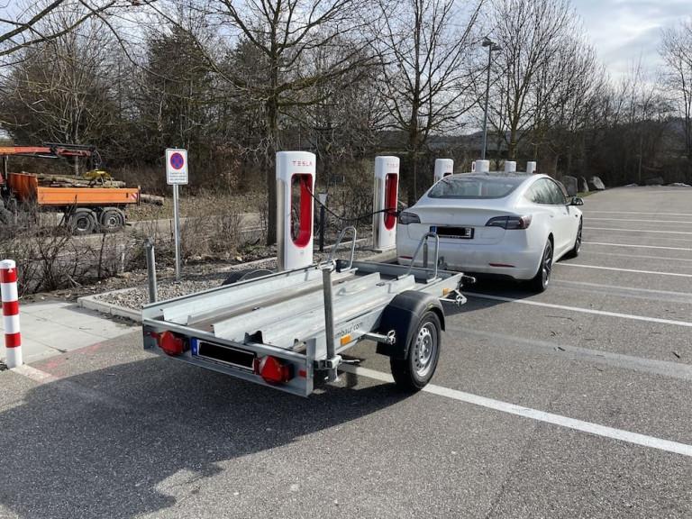 Tesla Model 3 mit Anhängerkupplung und Motorradanhänger am Tesla Supercharger