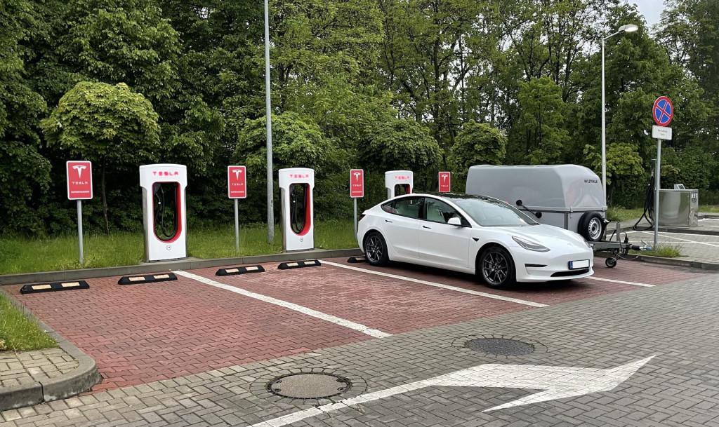 Ein Tesla Model 3 2021 Long Range mit Westfalia Anhänger an einem Tesla Supercharger in Katowice / Polen