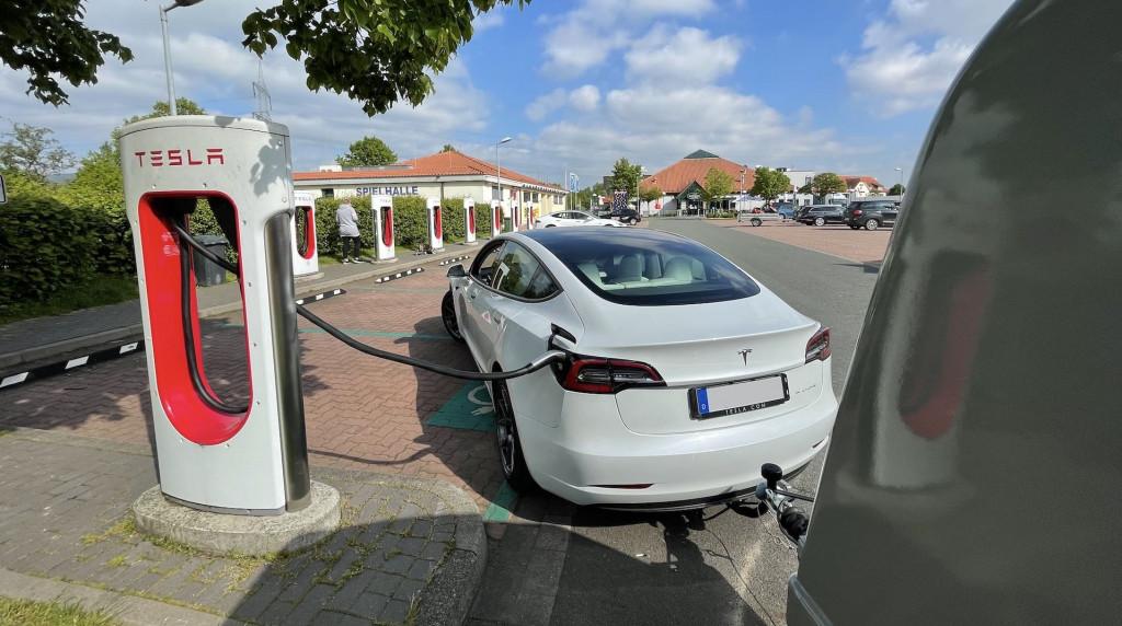 Ein Tesla Model 3 2021 Long Range mit Westfalia Anhänger an einem Tesla Supercharger